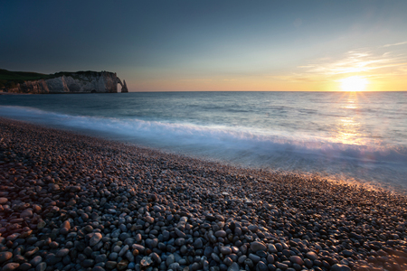 Sunset at the pebbled beach, Porte dAval and LAiguille at Etretat, a commune in the Seine-Maritime department in the Normandy region of north western France