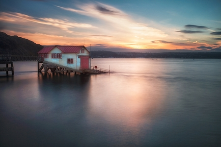 Sunset and a calm evening tide at the old lifeboat station in Mumbles, Swansea Bay, South Wales, UK Stock Photo