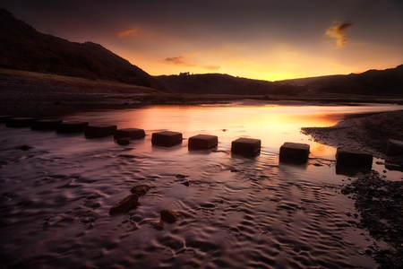 Sunrise at Three Cliffs Bay Sunrise over the stepping stones that allow access to the divided beaches at Three Cliffs Bay on the Gower peninsula in Swansea, South Wales, UK Stock Photo
