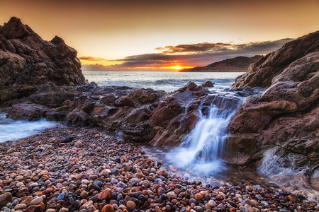 A small cascade of seawater as the tide swells on the beautiful coastline of Rotherslade Bay, a small bay in South Gower next to the more famous Langland Bay. Stock Photo