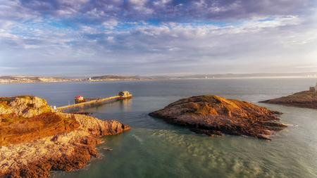 A calm morning at Mumbles Pier, an aerial view showing the new lifeboat station and the middle island, Swansea, South Wales, UK