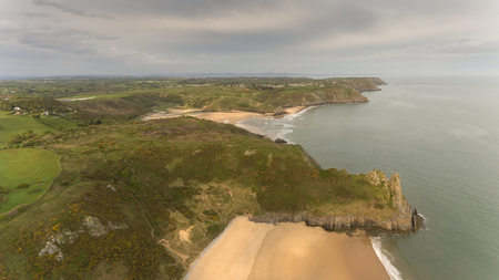 Aerial view of Tor Bay and The Great Tor on the Gower peninsula, Swansea, South Wales, UK