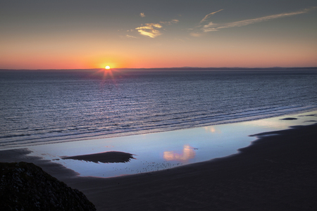 Solstice sunset 2018 over Rhossili Beach on the Gower peninsula in Swansea, South Wales, UK Stock Photo