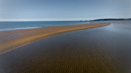 A sandbar in Swansea Bay exposed at very low tide, with Mumbles pier and lighthouse in the distance.