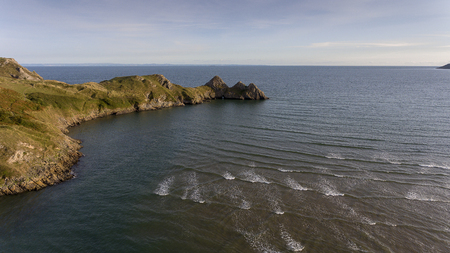 Aerial view of the incoming tide at the dramatic Three Cliffs Bay on the Gower peninsula, Swansea, South Wales, UK