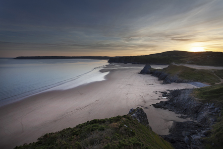 Sunset at Three Cliffs Bay and The Great Tor on the Gower peninsula, Swansea, South Wales, UK