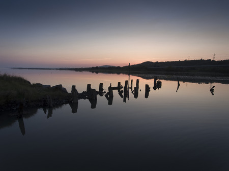 The remains of an old jetty and a high, calm tide on the river Neath in South Wales, UK.