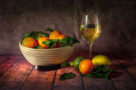 Citrus fruit and wine In the style of the old masters still life, a citrus fruit combination of lemons, limes and satsumas.