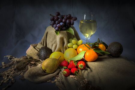 In the style of the old masters still life, a mixed fruit combination of lemons, limes, satsumas, strawberries, grapes, avocado and pear. Stock fotó