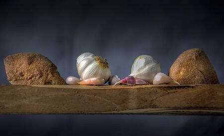 Garlic cloves and rustic bread rolls on a wooden board