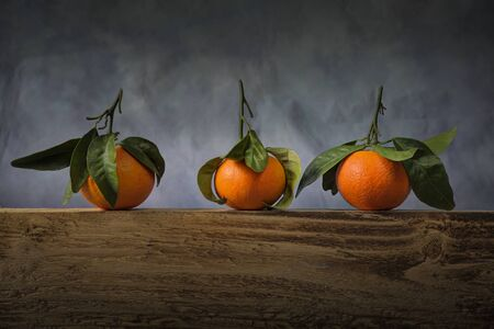 A trio of leaf bearing satsumas on a wooden board