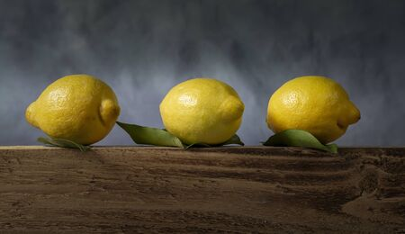 A trio of lemons on a wooden board