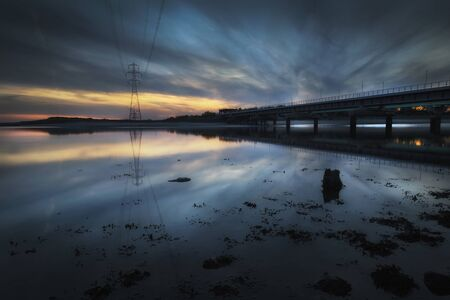 Sunset at the railway line crossing over the Loughor estuary from Swansea to Llanelli in South Wales, UK Stock fotó