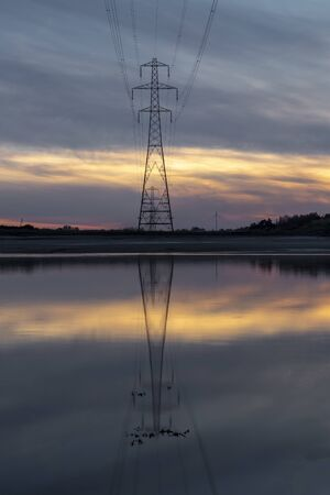 Pylon reflection in after sunset on the Loughor estuary, Llanelli, South Wales, UK