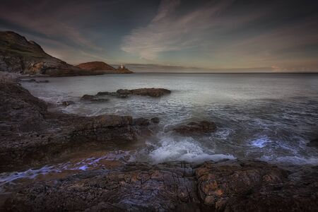 High tide over the rocks at dusk on Bracelet Bay and Mumbles Lighthouse on the Gower peninsula in Swansea, South Wales, UK.