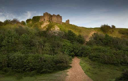 The remains of Pennard castle reflected in the valley river on the Gower peninsula, Swansea, South Wales, UK Stock fotó