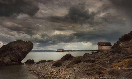 Dramatic storm clouds over Mumbles Pier and the coastguard and lifeboat buildings in Swansea, South Wales UK