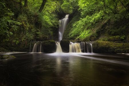 Situated along the river above Sgwd Gwladus falls, Sgwd Einion Gam is a difficult waterfall to access in the South Wales area known as Waterfall Country. Archivio Fotografico