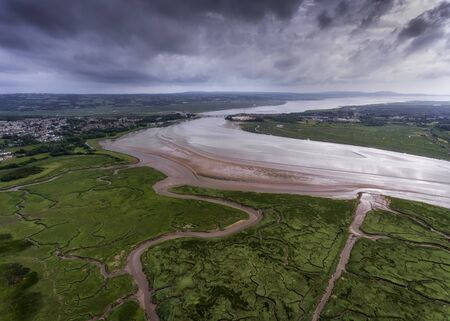 Storm clouds and tributaries at the Loughor estuary, Llanelli, South Wales, UK