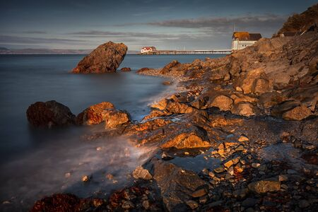 Dusk at Knab rock in Mumbles Evening sunlight and a long exposure of Knab Rock and Mumbles Pier in Swansea Bay, South Wales, UK Фото со стока