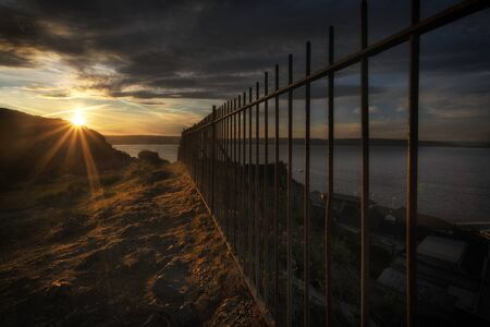 Sunset at the safety railings Evening at the safety railings that sit on the hill overlooking Mumbles Pier and lighthouse in Swansea, South Wales, UK