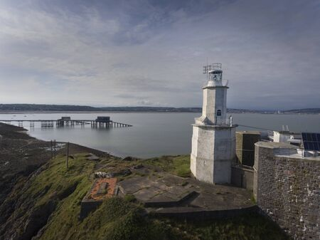 The iconic landmark that is Mumbles Lighthouse on the Gower peninsula in Swansea, South Wales, UK. Фото со стока