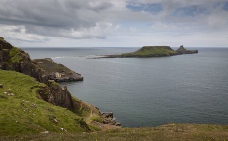 The dramatic cliffs and old boat house at Worms Head on the Gower peninsula in Swansea, South Wales, UK