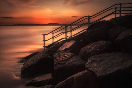 High tide at sunset, a long exposure and a handrail leading to the beach at Aberavon, Port Talbot, UK.