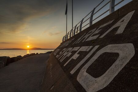 Sunset at the surfing area at Aberavon beach and the bilingual writing on the breakwater in Port Talbot, South Wales, UK