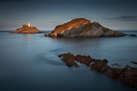 A long exposure at dusk of the landmark that is Mumbles Lighthouse on the Gower peninsula in Swansea, South Wales, UK. Фото со стока