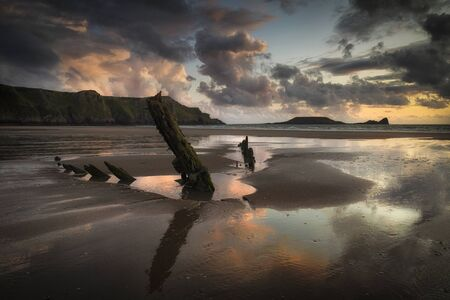 The Helvetia after the rain Rhossili Bay and Worms Head showing remains of the ship The Helvetia, a Norwegian barque, which was wrecked during a storm in 1887 on the Gower peninsula, South Wales, UK Фото со стока