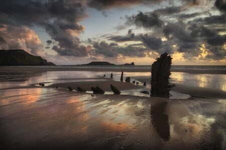 The remains of the Helvetia at Rhossili Bay, South Wales UK Rhossili Bay and Worms Head showing remains of the ship The Helvetia, a Norwegian barque, which was wrecked during a storm in 1887 on the Gower peninsula, South Wales, UK