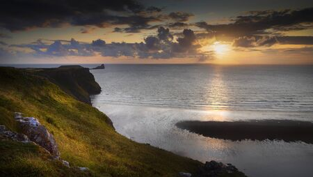 Sunset over the dramatic cliffs at Worms Head at Rhossili Bay on the Gower peninsula in Swansea, South Wales, UK