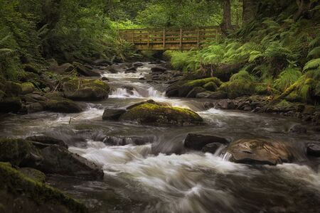 The bridge and rocky river bed at Melincourt Brook in Resolven, South Wales, UK