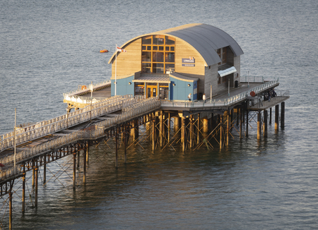 RNLI lifeboat house on Mumbles pier Editorial Swansea, UK - July 07, 2019: The RNLI lifeboat house and repair work continuing the refurbishment of Mumbles pier in Swansea, South Wales, UK