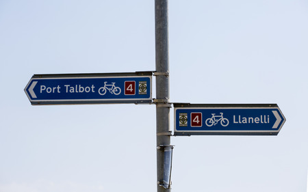 Editorial Swansea, UK - July 23, 2019: Welsh bicycle route signs showing distance to the nearest coastal towns to Swansea, South Wales, UK