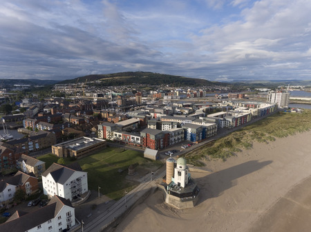 Editorial Swansea, UK - August 11, 2019: Aerial photo of the coastal housing development at the marina and the highest point in Swansea, Kilvey Hill.