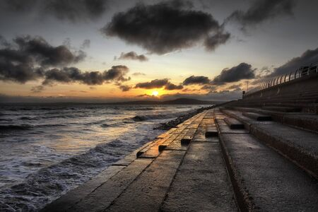 Sunset on the breakwater steps at Aberavon beach in Port Talbot, South Wales, UK