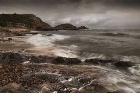 Wave movement at Bracelet Bay and Mumbles Lighthouse on the Gower peninsula in Swansea, South Wales, UK. Фото со стока