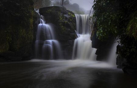 A close up long exposure of the waterfall at Penllergare Valley Woods easily accessible just off junction 47 of the M4 motorway in Swansea, UK. Imagens