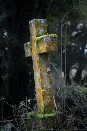 A weather beaten moss covered old marble cross or gravestone in an abandoned churchyard in South Wales, UK Imagens