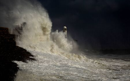 Porthcawl lighthouse and pier in the jaws of a storm on the coast of South Wales, UK. Archivio Fotografico