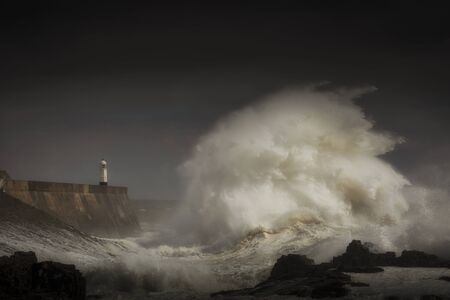 Porthcawl lighthouse and pier in the jaws of a storm on the coast of South Wales, UK.
