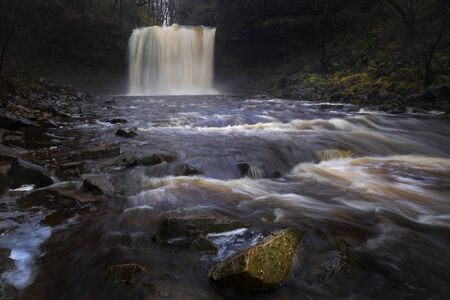 The Afon Hepste river plunging over a band of resistant gritstone to form the waterfall Sgwd yr Eira which translates into 'Fall of snow' and often referred to as the waterfall you can walk under.