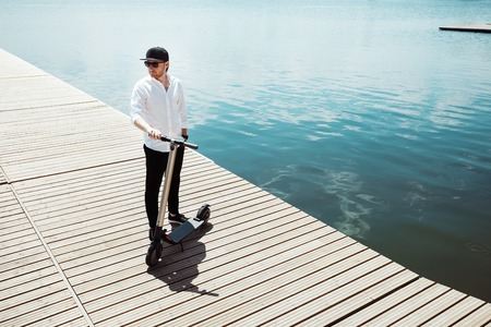 Photo of modern man with electric scooter at a wooden pier Stock Photo