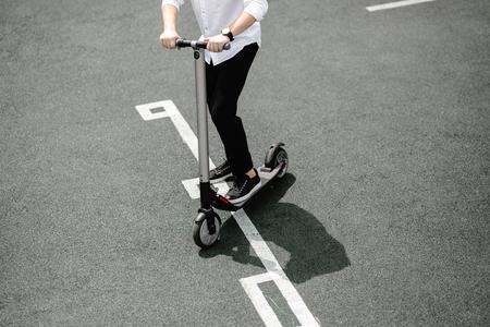 Le gambe di un uomo in abito elegante stanno su uno scooter elettrico sulla strada Archivio Fotografico