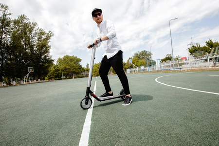Modern man in stylish black and white outfit riding electric scooter in the city Stock Photo