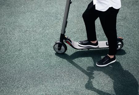 Le gambe di un uomo in abito elegante stanno su uno scooter elettrico sulla strada