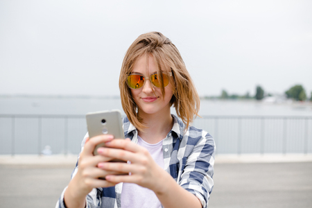 Young happy girl in hipster making selfie on phone
