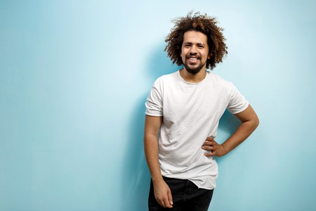 Smiling curly-headed man in white T-shirt with a hand on the hip. An easy going person with positive outlook. Happiness and joy in the eyes.